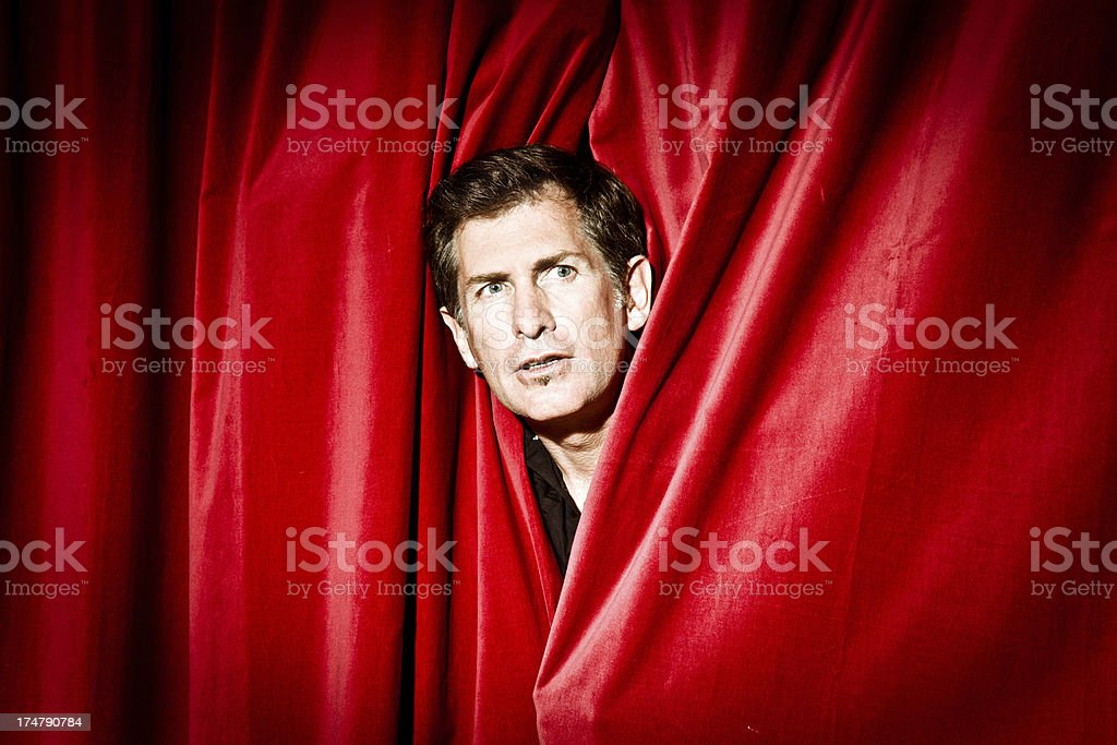 Actor peeking through curtain stock photo