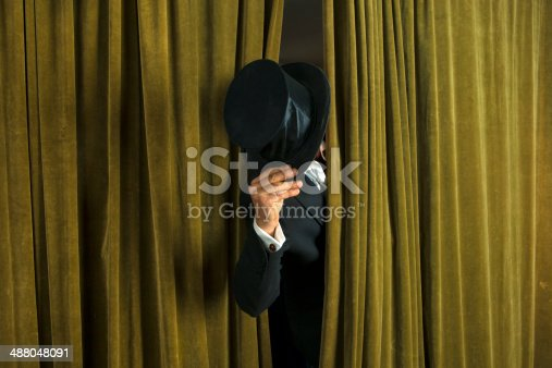 istock Actor with opera hat appears from behind the curtain. 488048091