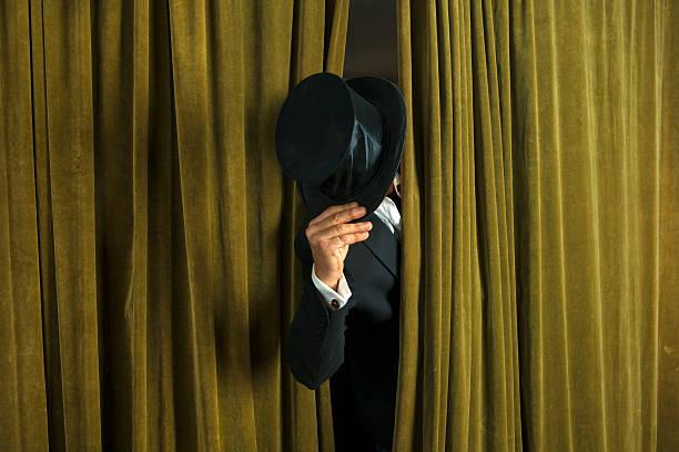 schauspieler mit opera-hut erscheint hinter dem vorhang. - mädchen vorhänge stock-fotos und bilder