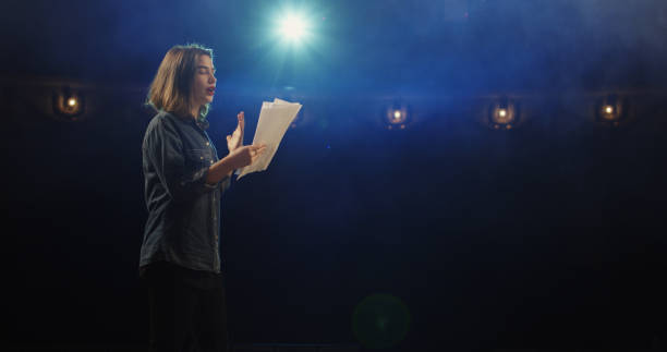 Actress rehearsing in a theater Medium close-up of an actress rehearsing a monologue in a theater while holding her script speech stock pictures, royalty-free photos & images