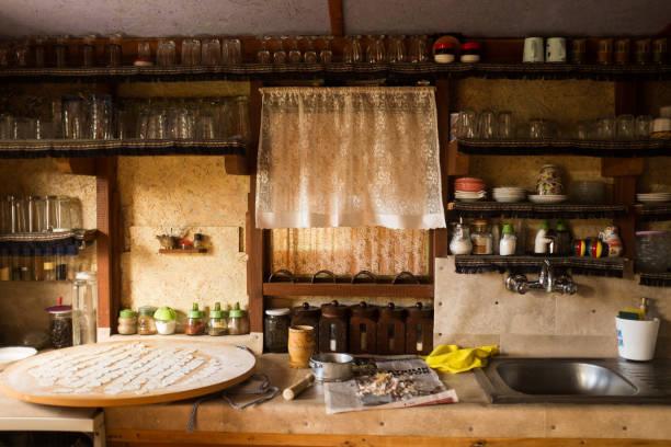 Tatsächliche rustikale Küche mit Utensilien zum Kochen. Tabelle im Vordergrund mit Kopierraum – Foto