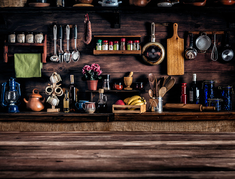 Actual rustic kitchen with utensils for cooking. Table at the foreground with copy space