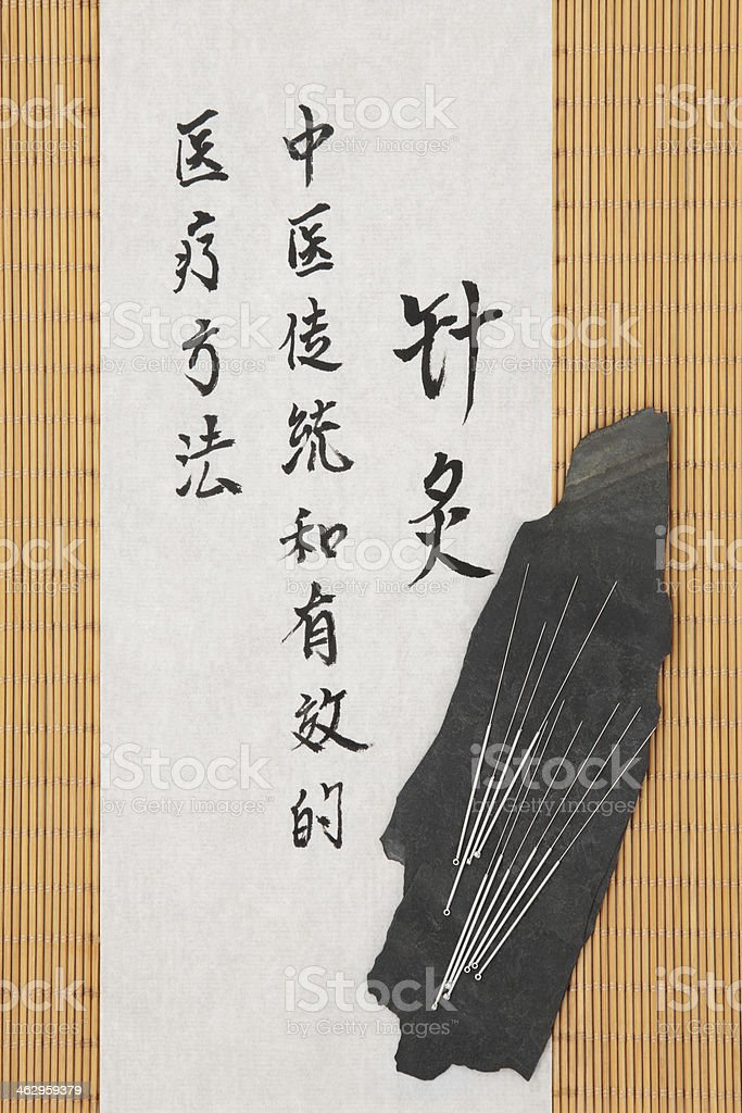 Acupuncture needles and mandarin script on rice paper over bamboo....