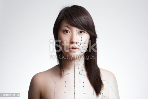 Composing of pictures from asian girl and acupuncture model. Concept for acupuncture, alternative medicine, holistic healing. Channels and numbers of acupoints partly visible.