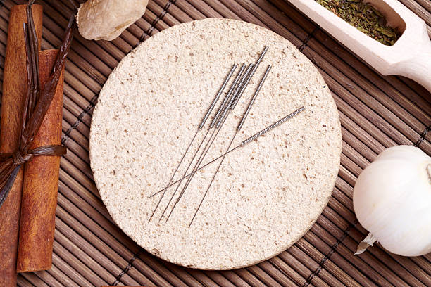 Acupuncture needles and TCM herbs stock photo