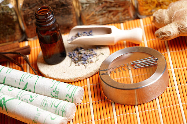 Acupuncture needles, moxa sticks and lavender petals Acupuncture needles, moxa sticks, lavender petals with macerated oil, giner and herbs in jars. TCM Traditional Chinese Medicine concept photo chinese herbal medicine stock pictures, royalty-free photos & images