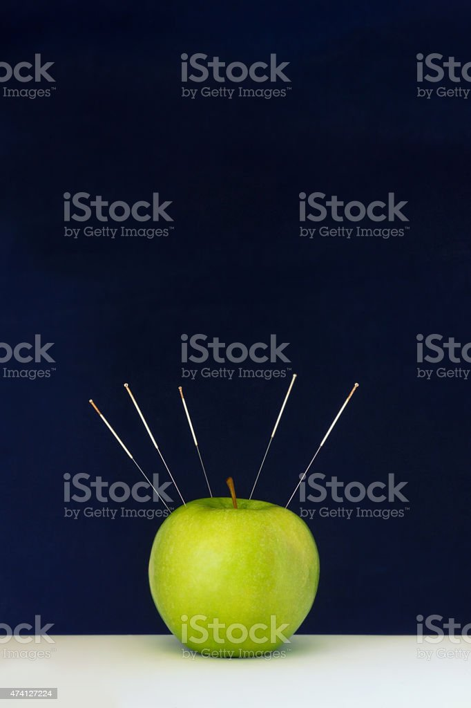 Acupuncture Needles Stuck Into A Green Apple As A Symbol Stock Photo