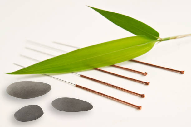 Acupuncture needles with bamboo leaf and stones background stock photo