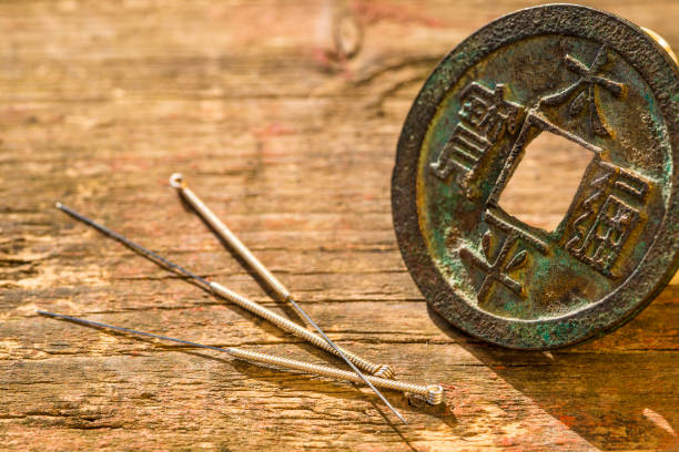acupuncture needles with chinese coin stock photo