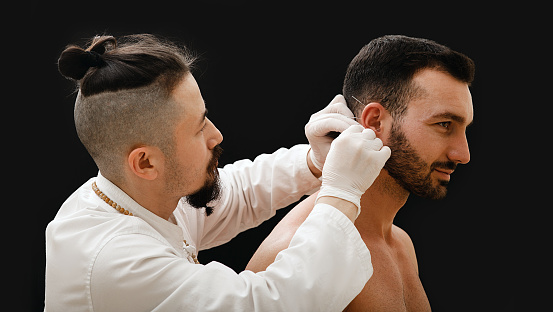 istock Acupuncturist insert acupuncture needles into patient's ear to cure him of smoking addiction. Close-up portrait of a patient with needles in his ear and a doctor on a black background 1217562615