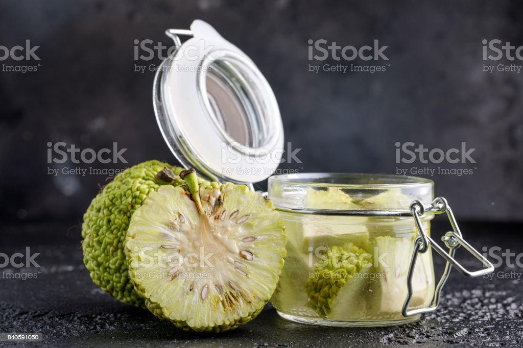 Adam's apple on a black background. Tincture of Adam's apple in a glass jar. stock photo