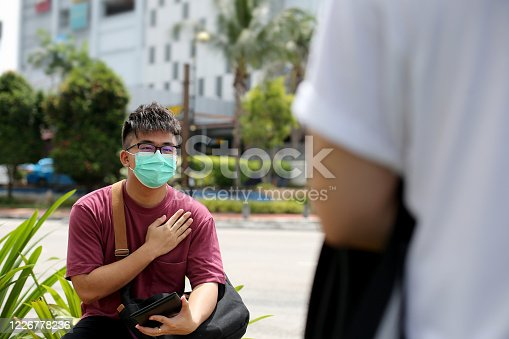 A young man wearing protective face mask placed his palm on chest when meeting with his friend at rendezvous point in Malaysia.