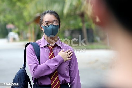 A teenage girl with school uniform and protective mask is placing her right hand on left chest (Malaysian way of greeting) as an alternative to handshake in Malaysia.