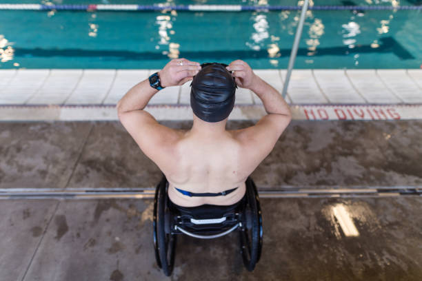 Adaptive athlete prepares to swim in a pool An adaptive athlete sits in his wheelchair and adjusts his swim cap before he gets in the pool for a training swim. The shot is from overhead and behind him. paraplegic stock pictures, royalty-free photos & images
