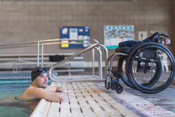 athlète adaptative s'apprête à nager dans une piscine - sports en fauteuil roulant photos et images de collection