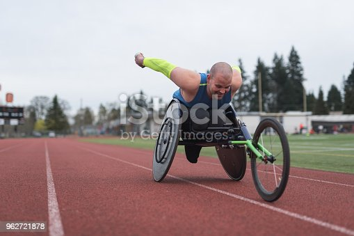A Caucasian para athlete trains at a stadium track in his wheelchair. He is racing toward the camera and has an intense expression.
