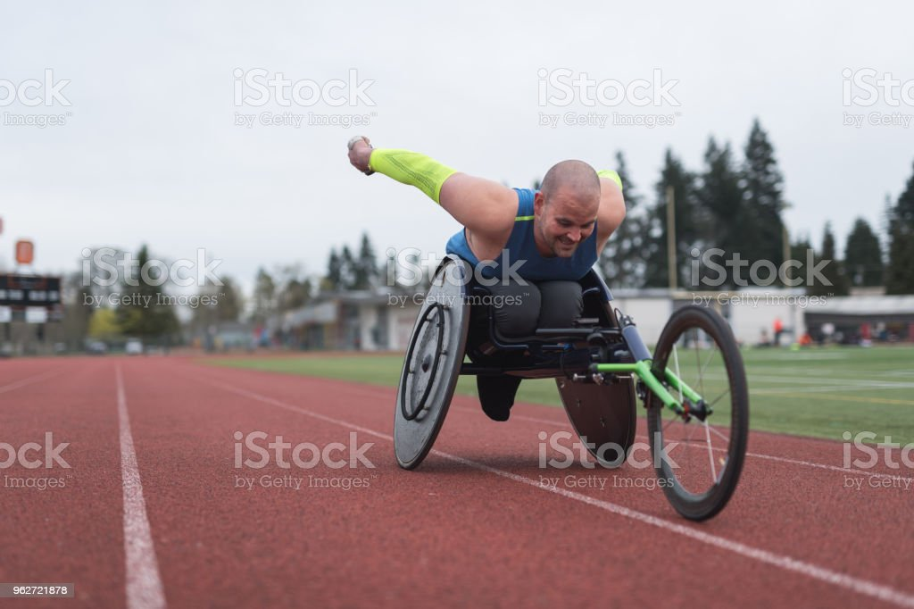 Adaptive athlete training on his racing wheelchair at a stadium track stock photo