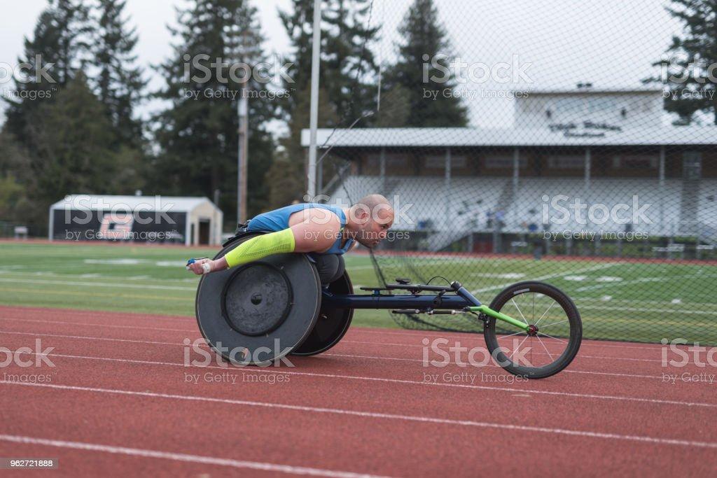 Adaptive Athlet training auf seinem Rollstuhl Racing auf einer Stadion-Strecke – Foto