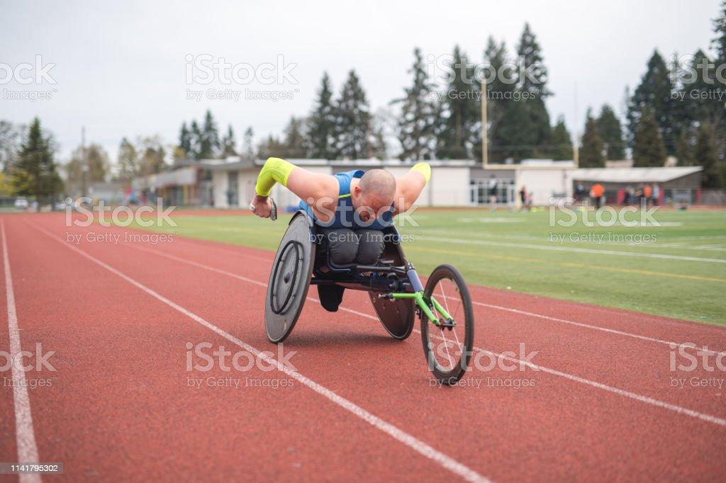 Adaptives Athletentraining auf seinem Rennrollstuhl auf einer Stadionstrecke – Foto