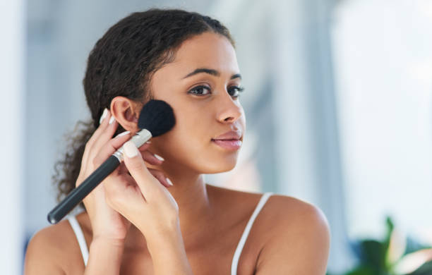 Add a dash of magic to each day Cropped shot of a young woman applying makeup to her cheeks in the bathroom at home blusher make up stock pictures, royalty-free photos & images