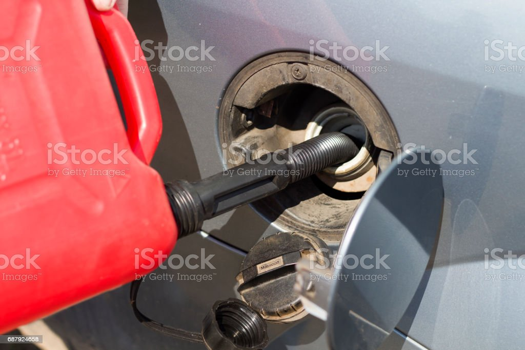 Add fuel from a plastic canister to the car's tank. stock photo