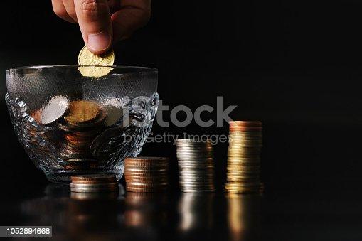 istock add saving coin to coin cup, money saving concept 1052894668