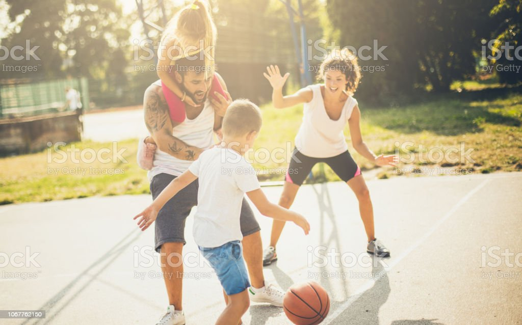 Add the ball and let your team win. Family playing basketball.