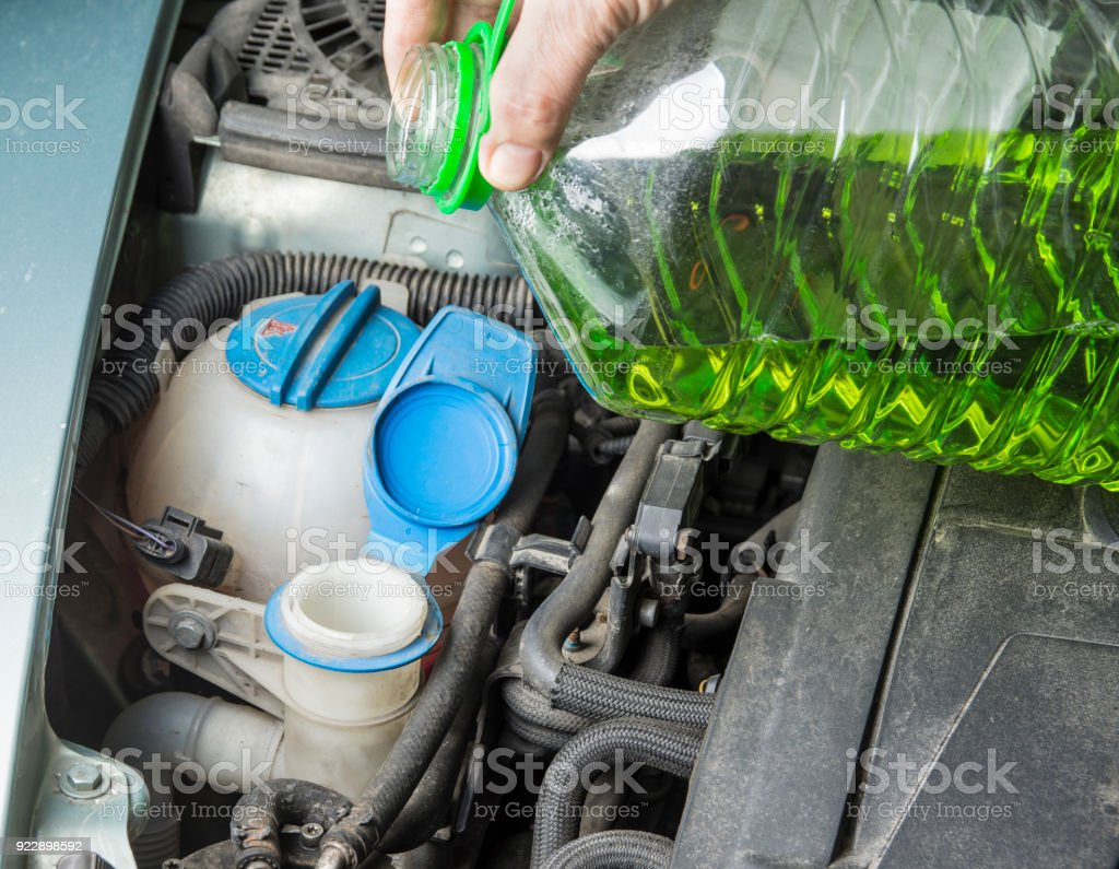 Add up windshield wiper summer fluid in car stock photo
