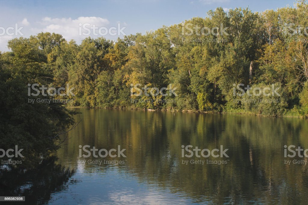 Adda river with trees reflected in the water and clear sky stock photo