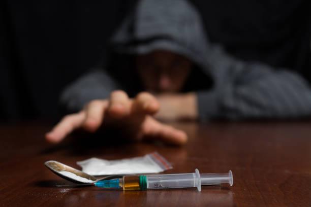 tossicodipendente a tavola tira la mano alla siringa con la dose - assuefazione foto e immagini stock