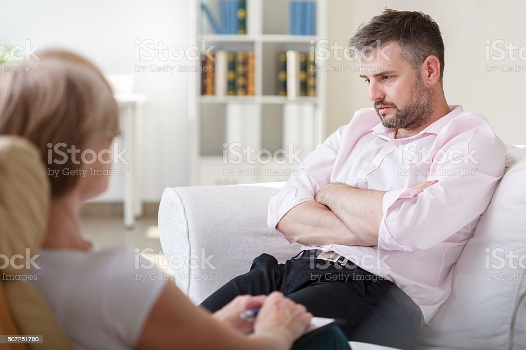 Addicted businessman on psychotherapy session stock photo