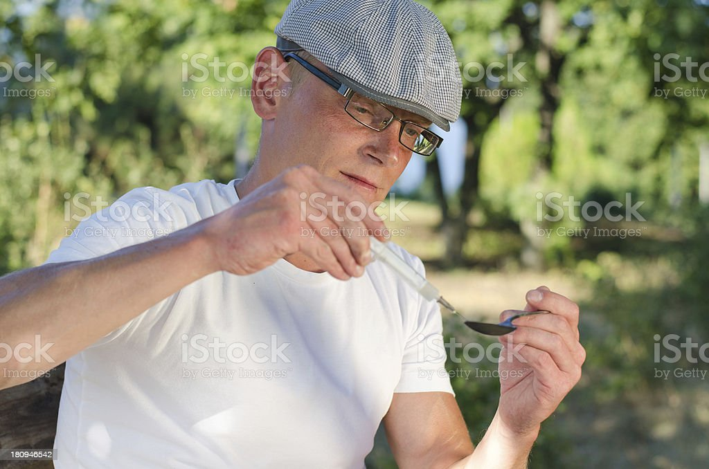 Addicted man filling a syringe with soluble heroin royalty-free stock photo