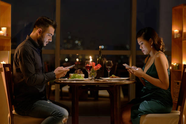 Addicted to smartphones Young people checking their smartphones during romantic date in restaurant asian couple arguing stock pictures, royalty-free photos & images