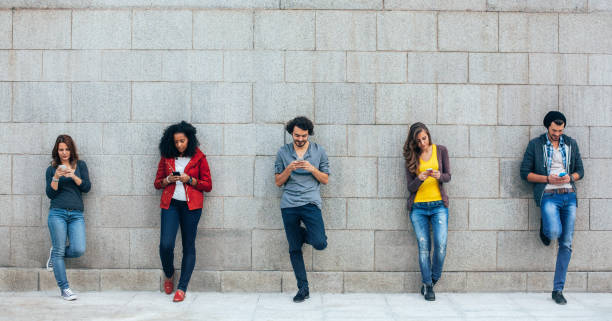 Addicted to social media Friends leaning to wall using smartphones digital native stock pictures, royalty-free photos & images