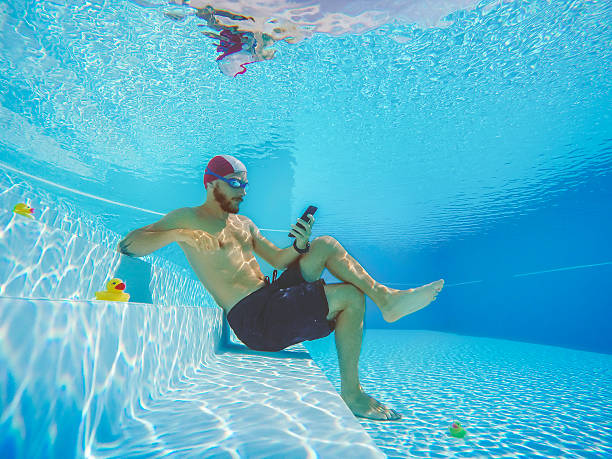 Addicted to social networking: with mobile phone underwater stock photo