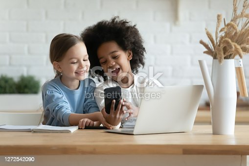 Addicted to technology overjoyed little mixed race kids sisters looking at mobile phone scree, using funny photo application, recording video for social networks or playing online games at home.