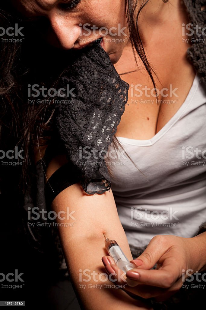 Addicted woman injecting drugs into her veins stock photo