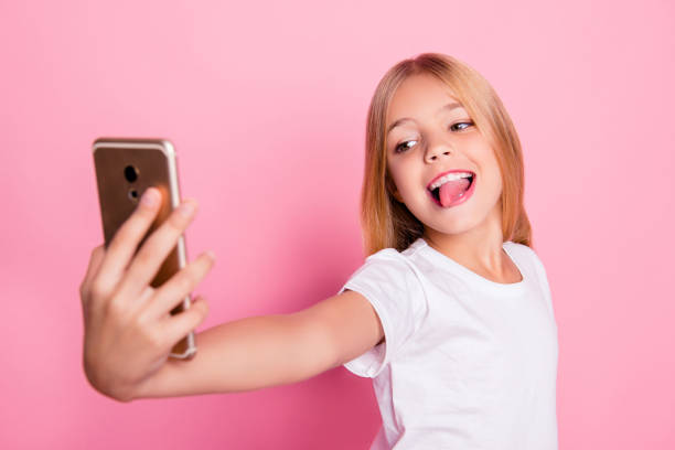 addiction lifestyle leisure style trend play game concept. close up portrait of cute lovely sweet charming with toothy smile taking selfie girl on mum's phone isolated on pink background - tween models stock photos and pictures