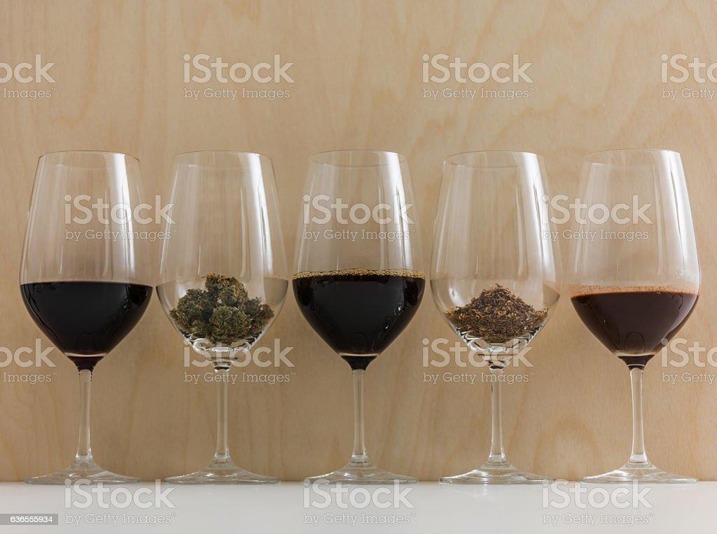 Addictions coffee, chocolate, wine, cannabis, tobacco in wineglasses. stock photo