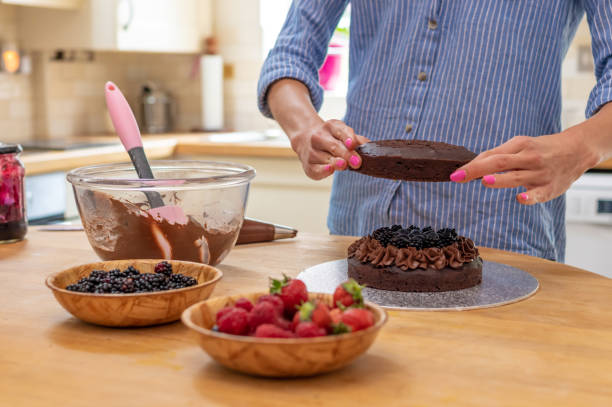 Adding a second layer to a chocolate cake stock photo