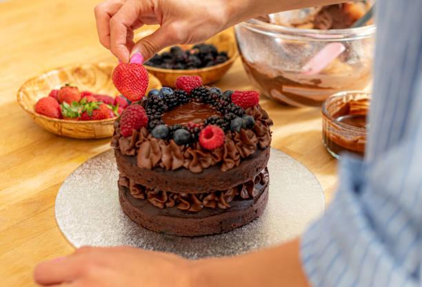 Adding a strawberry to a chocolate cake stock photo