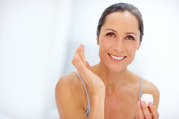 Adding a touch of moisture Shot of an attractive mature woman applying moisturizer to her skin one mature woman only stock pictures, royalty-free photos & images