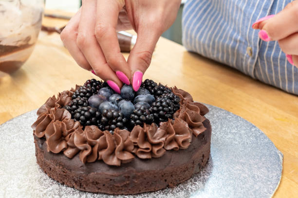 Adding blueberries and blackberries to a chocolate cake stock photo