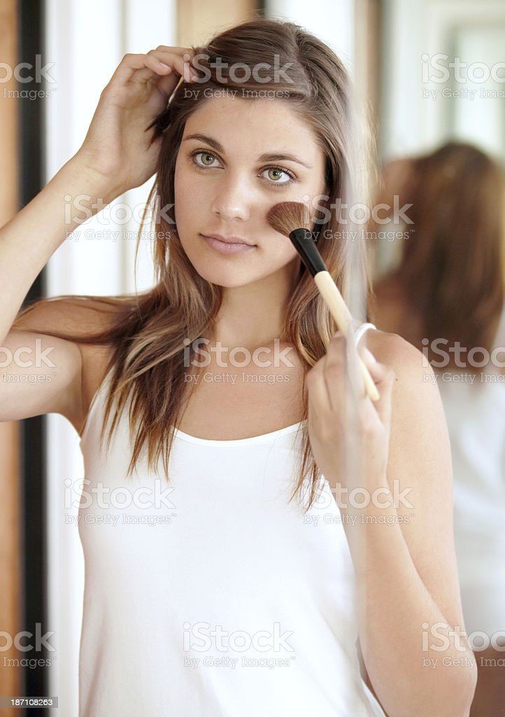 Adding blusher to her cheeks royalty-free stock photo