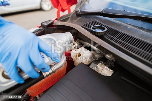 Close-up of an unrecognisable young caucasian man adding brake fluid to a car.