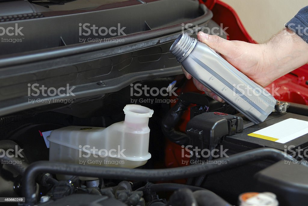 Adding brake fluid to a Car stock photo