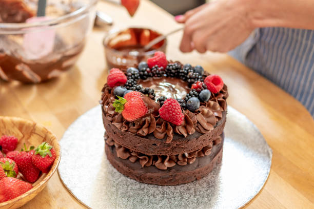 Adding fruit to a chocolate cake stock photo
