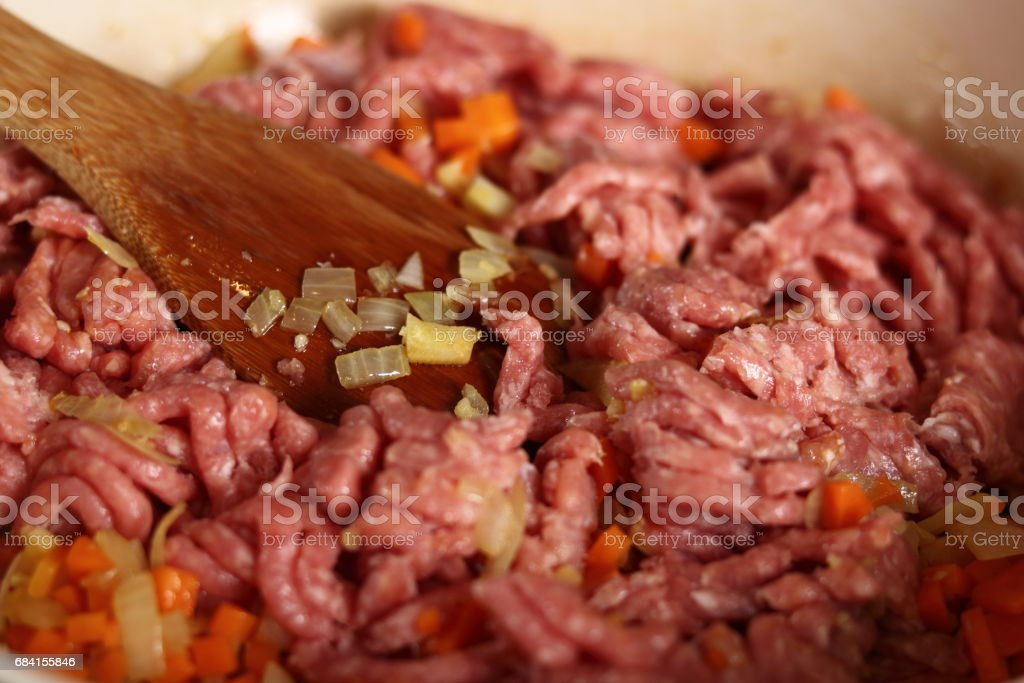 Adding ground meat into frying pan. Making Lasagna Bolognese Series. stock photo