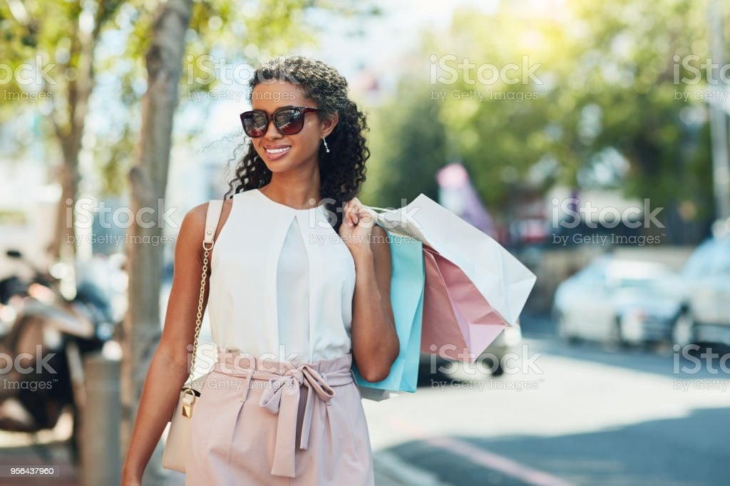 Adding items to my closet Shot of an attractive young woman going shopping in the city 20-29 Years Stock Photo
