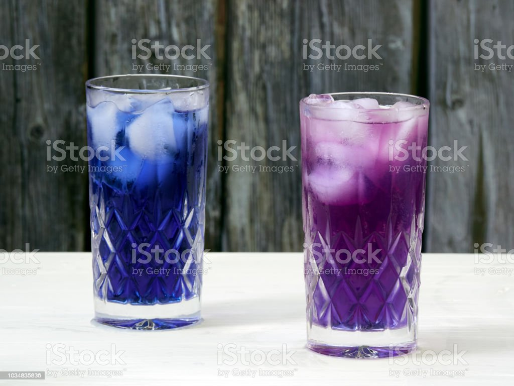 Adding lemon juice to a glass filled with layered butterfly pea flowers ice tea stock photo